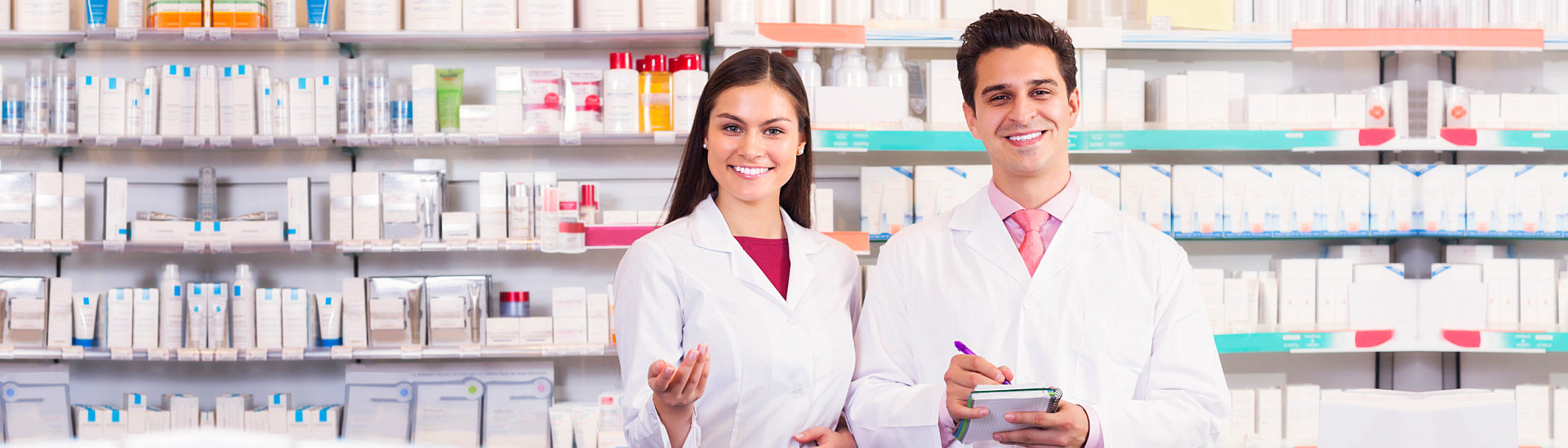 Positive pharmacist and pharmacy technician posing in drugstore