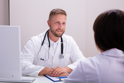 Doctor With Stethoscope Talking With Nurse At Desk